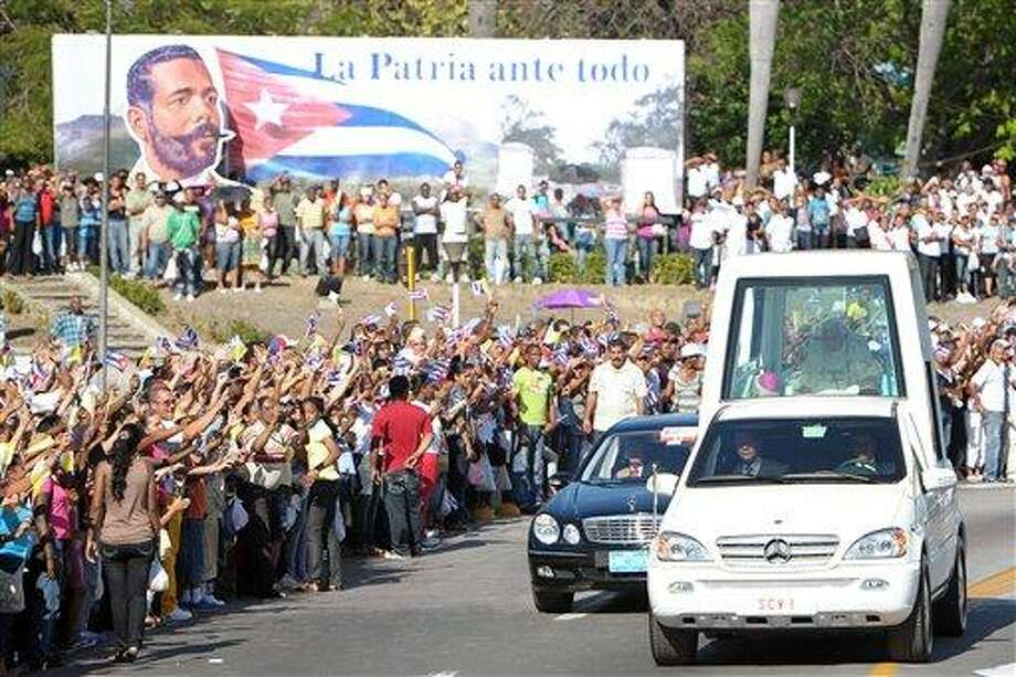 "In this picture made available Tuesday, March 27, 2012, by the Vatican newspaper Osservatore Romano, Pope Benedict XVI rides in the popemobile as people gather along the roadside to greet him upon his arrival Monday in Santiago de Cuba. The sign at top reads in Spanish ""Country before all."" Associated Press Photo: AP / OSSERVATORE ROMANO"