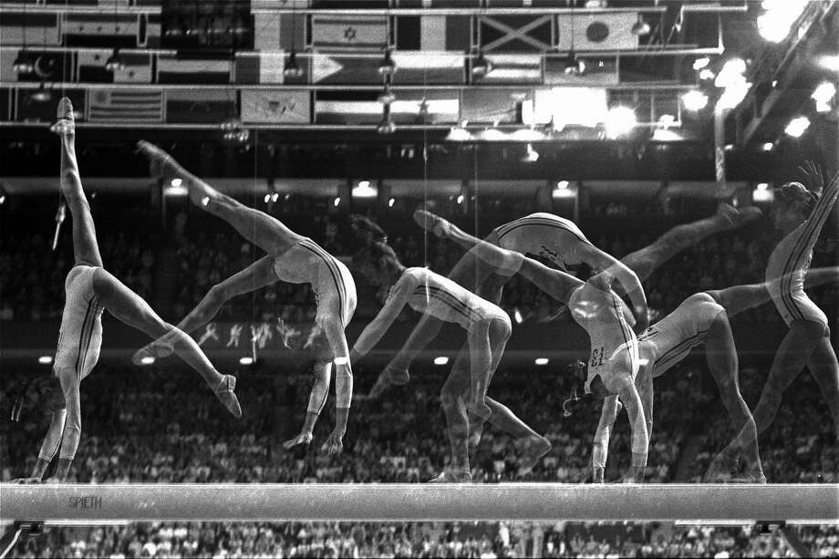 Romania's Nadia Comaneci, 14, performs her part of the balance beam routine Thursday July 23, 1976 in Olympic competition in Montreal.  This multiple exposure study points out the grace of her movements, leading to a gold medal and a perfect score in the event.  (AP Photo/Suzanne Vlamis) Photo: AP / 1976 AP