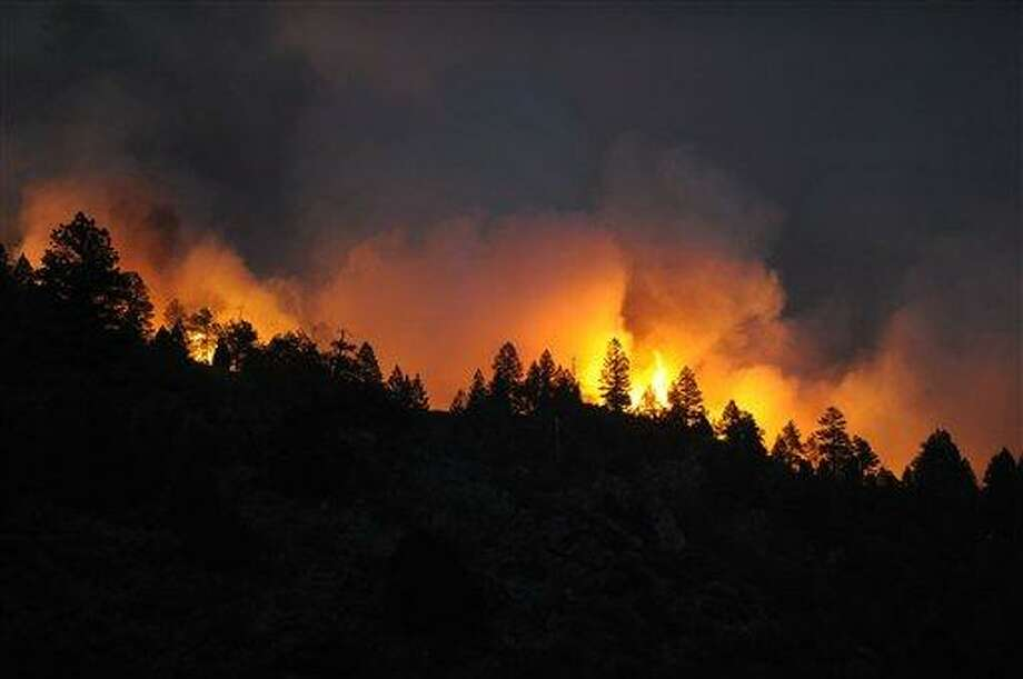 A fast-spreading wildfire comes over the ridge near Reynolds Ranch Monday in Conifer, Colo. Associated Press Photo: AP / (C) 2012 The Denver Post, MediaNews Group