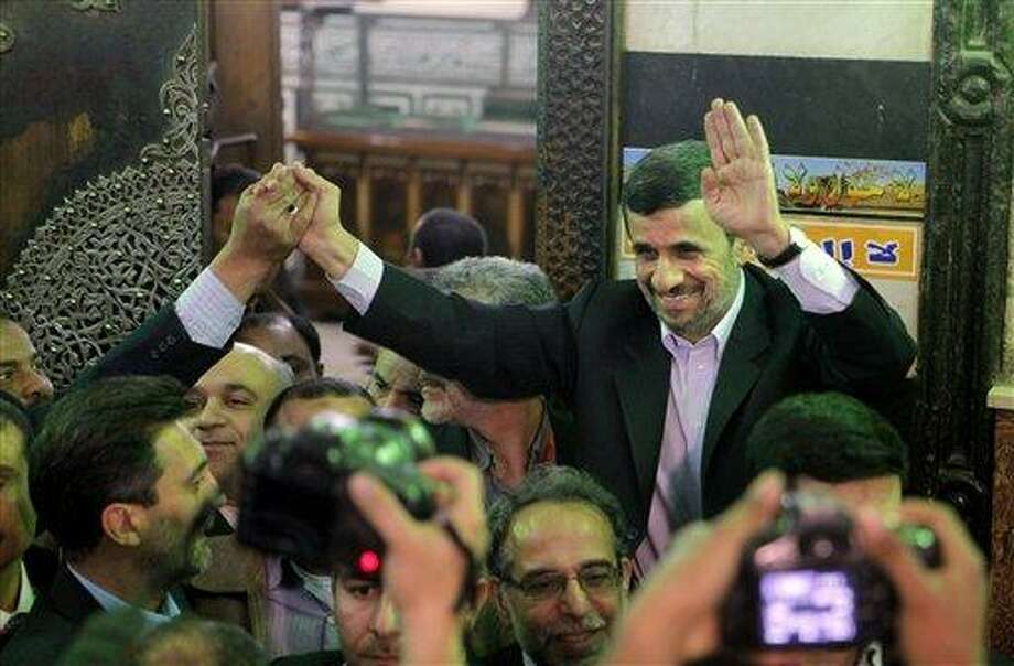 Iran's President Mahmoud Ahmadinejad, center, waves to Egyptians worshippers in front of the shrine of Imam Hussein, the grandson of Islam's Prophet Mohammad, in Cairo, Egypt, Tuesday, Feb. 5, 2013. Egypt's most prominent Muslim cleric, the sheik of Al-Azhar, has warned Iranian President Mahmoud Ahmadinejad against interfering in Arab Gulf countries or trying to spread Shiite influence. Ahmadinejad, on a landmark visit to Egypt on Tuesday, received an uneasy reception from Ahmed el-Tayeb at Al-Azhar, the Sunni Muslim world's foremost Islamic institution.(AP Photo/Amr Nabil) Photo: AP / AP