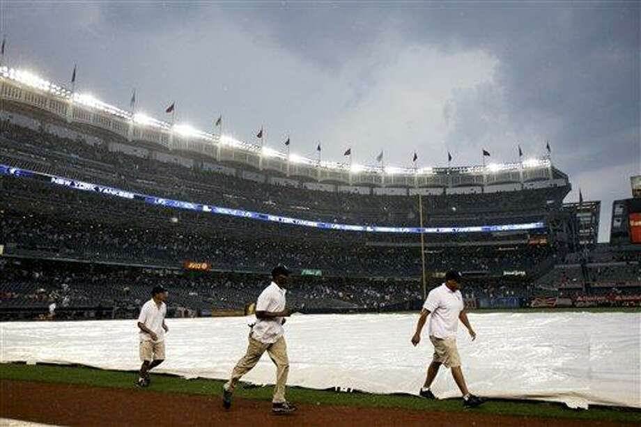 The grounds crew covers the field during a rain delay in the seventh inning of a baseball game between the New York Yankees and Toronto Blue Jays, Wednesday, July 18, 2012, at Yankee Stadium in New York. (AP Photo/Seth Wenig) Photo: AP / AP