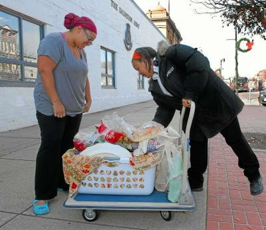 Michele Foye, at right, an employee at the Salvation Army, shows Middletown resident Marilyn Dunkley, a mother of six, what type of items are in the Thanksgiving basket she received at the Salvation Army on Main Street in Middletown Wednesday afternoon. Catherine Avalone/The Middletown Press