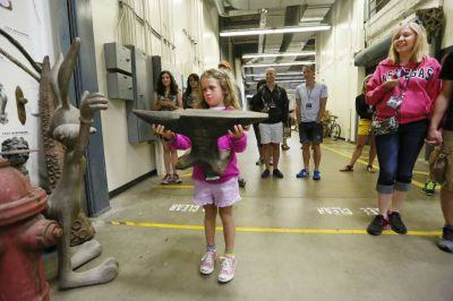 """This photo taken Wednesday, June 5, 2013 shows tourist Lisa Halloran, 8, holding a foam prop anvil from """"The Coyote and The Road Runner"""" cartoons series on the VIP Experience at Universal Studios Hollywood in Los Angeles. Many theme parks now have VIP tours with perks usually reserved for celebrities _ private tour guides, no waits for the biggest attractions, reserved seating at shows and parades along with behind-the-scenes peaks at places normally off limits. (AP Photo/Damian Dovarganes) Photo: AP / AP"""