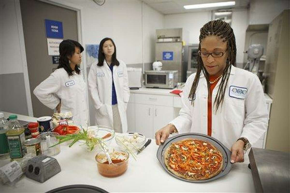 Lockeed Martin senior research scientist Maya Cooper shows a vegan pizza developed at NASA's Advanced Food Technology Project at Johnson Space Center July 3 in Houston. NASA is currently planning a mission to Mars, which has gravity, so more options for food preparation, like chopping vegetables, are available as opposed to the dehydrated fare of current space missions. Associated Press