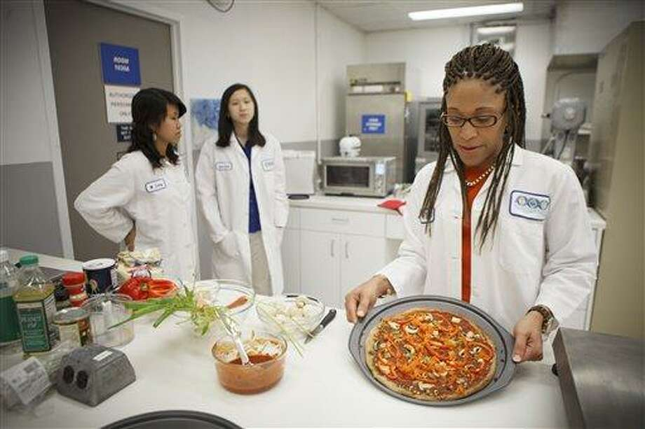 Lockeed Martin senior research scientist Maya Cooper shows a vegan pizza developed at NASA's Advanced Food Technology Project at Johnson Space Center July 3 in Houston. NASA is currently planning a mission to Mars, which has gravity, so more options for food preparation, like chopping vegetables, are available as opposed to the dehydrated fare of current space missions. Associated Press Photo: AP / FR29619 AP