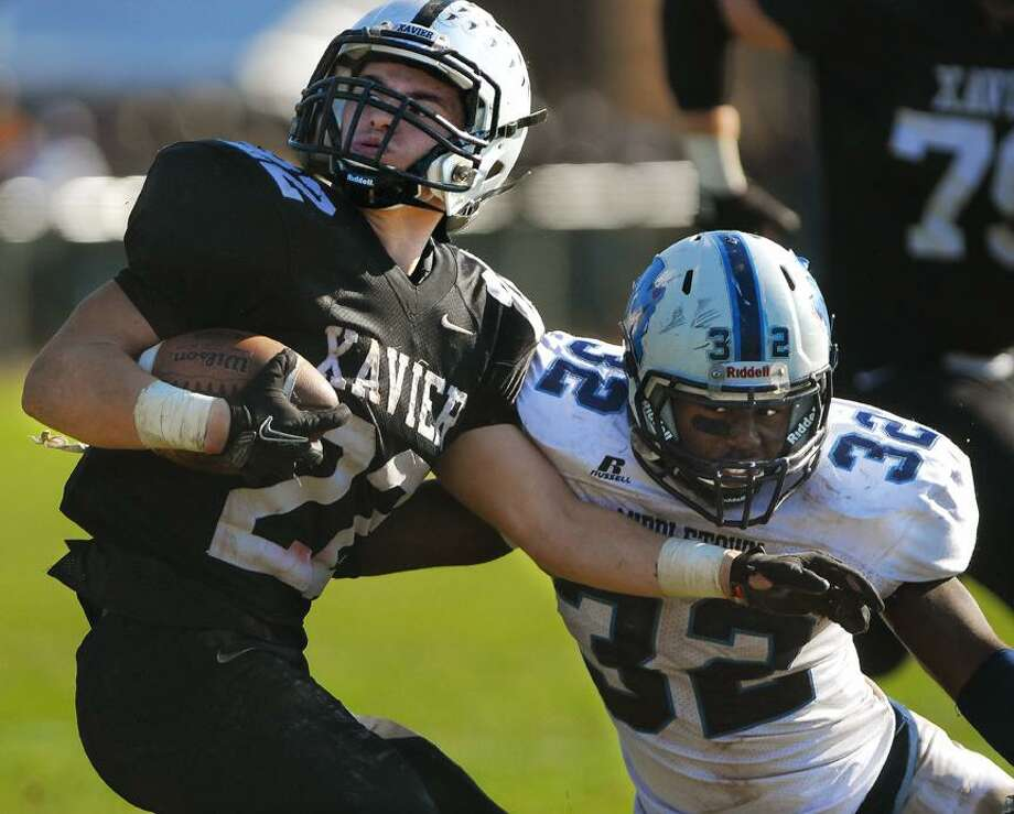 Catherine Avalone/The Middletown PressMiddletown senior Akeino Chamberlain attempts to pull down Xavier senior Kris Luster during the annual Thanksgiving Day game at Corwin Stadium at Wesleyan University Thursday morning. Xavier won, 41-