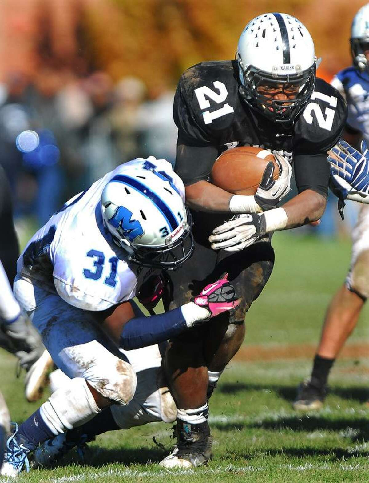 Catherine Avalone/The Middletown PressXavier senior running back DeAngelo Berry fights off Middletown senior running back Yaamal Jackson during the annual Thanksgiving Day game at Corwin Stadium at Wesleyan University Thursday morning. Xavier won, 41-