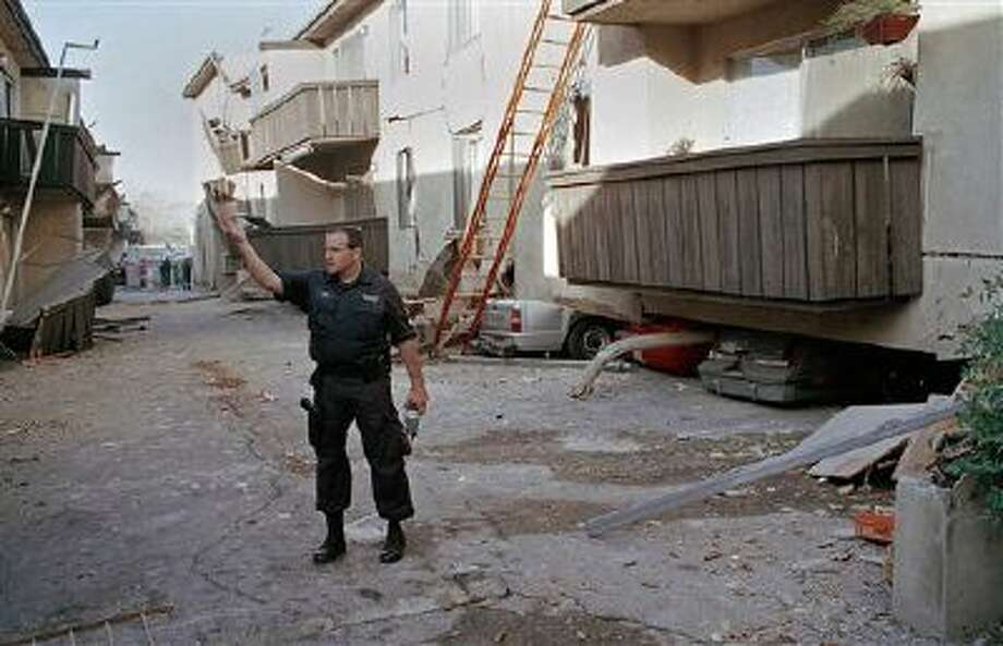 """A Los Angeles police officer stands in front of the Northridge Meadows Apartment building Jan. 17, 1994, after the upper floors of the structure collapsed onto the open garages and first story, killing 16 people. Los Angeles hopes to follow San Francisco's lead in upgrading so-called """"soft-story"""" buildings, multi-story structures with open first floors such as store fronts or garages that are in danger of collapsing during an earthquake. Photo: AP / AP"""