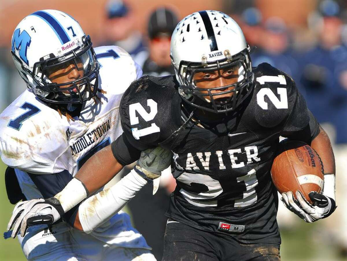 Catherine Avalone/The Middletown Press Xavier senior running back DeAngelo Berry shakes off Middletown's Isiah Swain during the fourteenth annual Thanksgiving Day game at Corwin Stadium at Wesleyan University Thursday morning. Xavier won, 41-14.