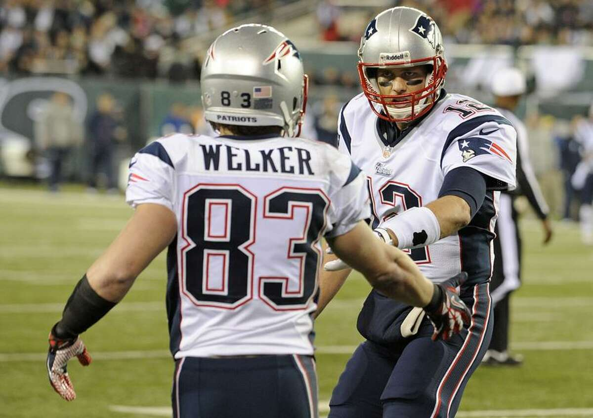 New England Patriots quarterback Tom Brady, right, celebrates with teammate Wes Welker (83) after the two connected for a touchdown during the first half of an NFL football game against the New York Jets, Thursday, Nov. 22, 2012, in East Rutherford, N.J. (AP Photo/Bill Kostroun)