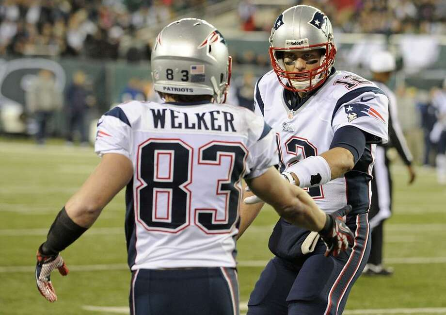 New England Patriots quarterback Tom Brady, right, celebrates with teammate Wes Welker (83) after the two connected for a touchdown during the first half of an NFL football game against the New York Jets, Thursday, Nov. 22, 2012, in East Rutherford, N.J. (AP Photo/Bill Kostroun) Photo: AP / AP2012