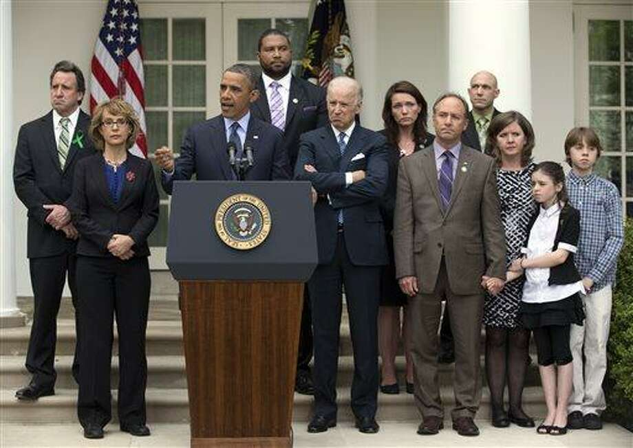 FILE - In this April 17, 2013 file photo President Barack Obama speaks in the White House Rose Garden of the White House about measures to reduce gun violence with former Rep. Gabby Giffords and family of victims of the Sandy Hook elementary school shooting. Six months after a gunman took their children's lives, some family members are headed back to Capitol Hill this week to remind lawmakers they are painfully waiting for action. From left are Neil Heslin, who lost his son Jesse Lewis; Giffords; Jimmy Greene, who lost his daughter Ana; Vice President Joe Biden; Nicole Hockley, who lost her son Dylan; Mark and Jackie Barden, with their children Natalie and James, who lost their son Daniel; and Jeremy Richman, behind the Barden's, who lost his daughter Avielle. (AP Photo/Carolyn Kaster, File) Photo: AP / AP