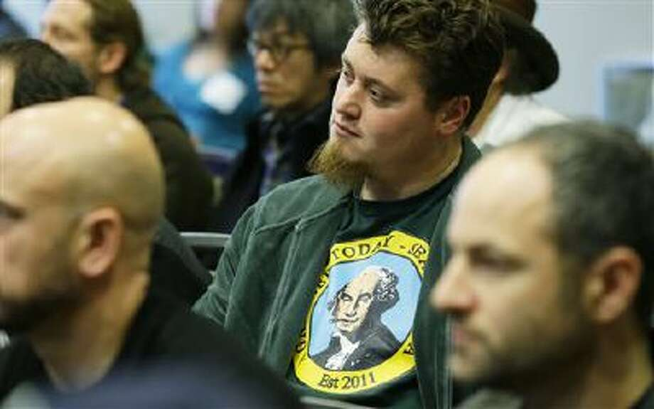 """Matt Dyson, owner of the medical marijuana dispensary """"A Greener Today,"""" wears a business t-shirt that features George Washington smoking a joint as he listens to questions, Monday, Oct. 21, 2013, at a workshop put on by the Washington Liquor Control Board in Seattle for people hoping to apply for business licenses to sell, process, or grow marijuana for legal retail sales in the state. Photo: AP / AP"""