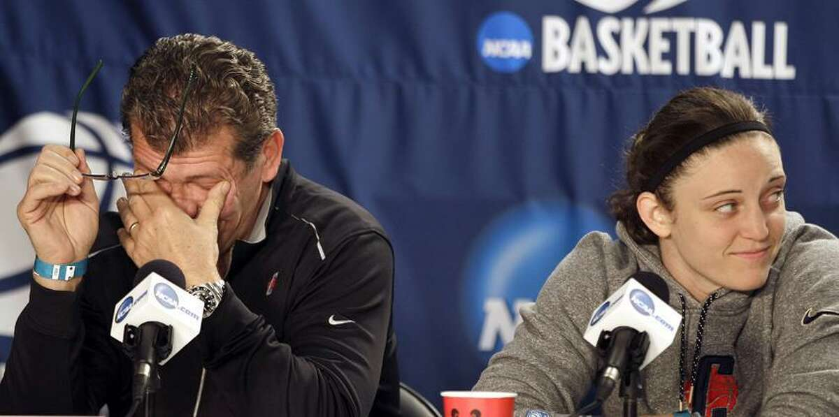 Connecticut head coach Geno Auriemma rubs his eyes and Connecticut guard Kelly Faris looks on while a teammate speaks during an NCAA college basketball news conference in Kingston, R.I., Monday, March 26, 2012. Connecticut is scheduled to play Kentucky in a women's NCAA tournament East Regional final college basketball game on Tuesday in Kingston. (AP Photo/Stephan Savoia)
