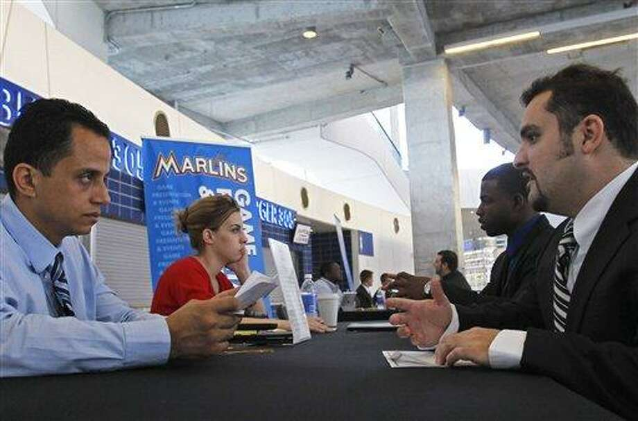 Job applicant Rafael Rodriguez, right, is interviewed Oct. 24 by Eric Ramirez, manager of game presentation and video production, at Marlins Park in Miami. Associated Press Photo: ASSOCIATED PRESS / AP2012