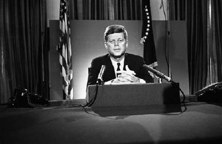 U.S. President John F. Kennedy sits behind microphones at his desk in Washington on July 26, 1963, after finishing his radio-television broadcast to the nation on the nuclear test ban agreement initialed by negotiators in Moscow. (AP Photo/John Rous) Photo: AP / AP