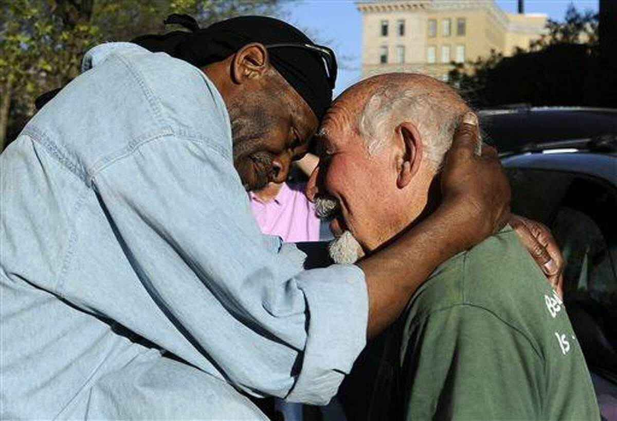 FILE - In this May 1, 2013 file photo, Michael Johnson, left, hugs friend Anthony Cymerys, known as Joe the Barber, in Bushnell Park in Hartford, Conn. For more than 20 years, Cymerys, 82, cut hair alfresco in Hartford for the fee of a hug. On Wednesday, June 13, 2013, Cymerys said as he was setting up, health officials and police told him and his friends, who hand out food to the needy, had to leave because they didn't have permits. (AP Photo/Jessica Hill, File)