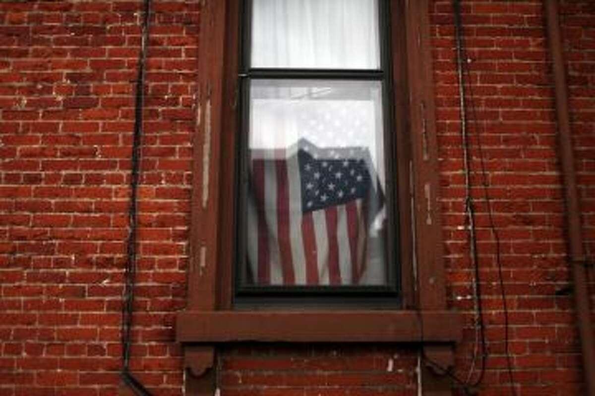 A flag hangs in a window in Utica, NY.