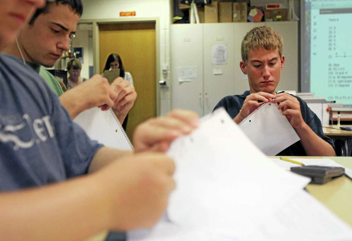 In this Sept. 19, 2013 photo, Caleb Janssen, a sophomore at Mattawan High School, tears off the ends of loose leaf paper at Mattawan High School in Mattawan, Mich.