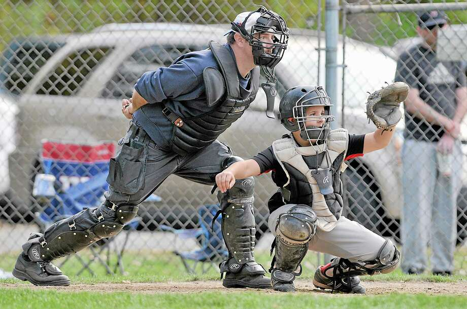 Three generations and 56 years later, 9-year-old catcher Zachary Robert Zajac is behind the plate for the Cromwell Blacks against the Deep River Cubs Saturday afternoon at Richard Baroni Memorial Field at Hubbard Park in Middletown. The field is named in memory of Zach's great uncle, Richard Robert Baroni, a young catcher for the Kiwanis Little League team who died at age 10 after falling through the ice at Pameacha Pond. The field was named in his memory shortly after. Photo: Catherine Avalone - The Middletown Press   / TheMiddletownPress