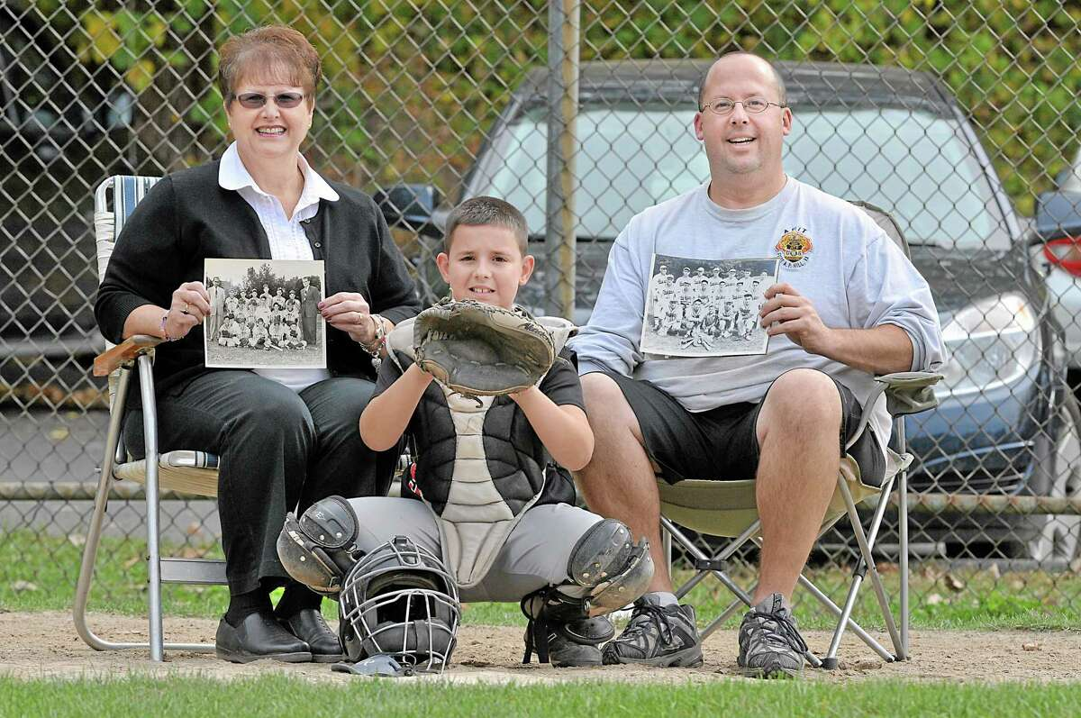 Sandy Baroni Zajac, left, holds a 1955 photograph of her older brother's baseball team, the Kiwanis. Sandy was 5 years old when Richard fell through ice at Pameacha Pond in January 1957 and drowned. Saturday, her 9-year-old grandson, Zachary Robert Zajac, center, took the field. He is the son of Rob Zajac, right, a South District firefighter who also played at Hubbard Park in 1982 for Sunshine Dairy. Rob Zajac is holding a picture of his grandfather, Robert Baroni, one of the founders of Hubbard Park who played catcher and third base for the Middletown Giants.