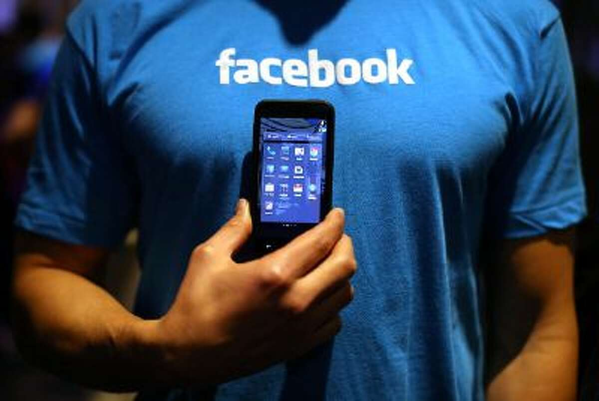 """A Facebook employee holds a phone that is running the new """"Home"""" program during an event at Facebook headquarters during an event at Facebook headquarters on April 4, 2013 in Menlo Park, California."""