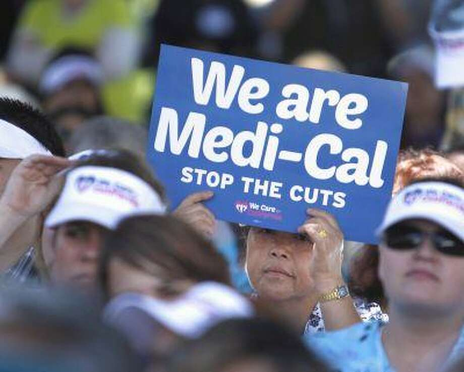 Sign carrying demonstrators representing doctors, hospitals and unionized health care workers rallied against a 10 percent cut in the amount the state pays for Medi-Cal reimbursements, at the Capitol in Sacramento, Calif., Tuesday, June 4, 2013. The protestors called for Gov. Jerry Brown and the Legislature to restore the reimbursement rate for the coming fiscal year, which starts July 1.(AP Photo/Rich Pedroncelli) Photo: AP / AP