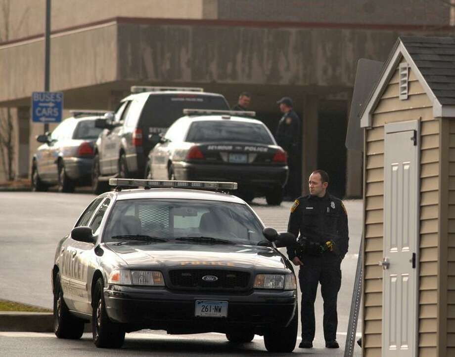 Police at the entrance to Newtown High School during the day on Tuesday. Mara Lavitt/New Haven Register  12/18/12