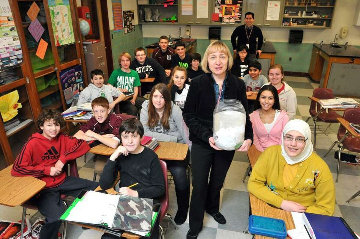 """North Haven-- North Haven Middle School science teacher Clara Laster, with her students are participating in """"26 Acts of Kindness"""" at the school. She is holding a jug containing some of the notes describing each act that the students have done so far. The 26 acts of kindness represent the victims of the Sandy Hook shootings. Photo-Peter Casolino 1/28/13"""