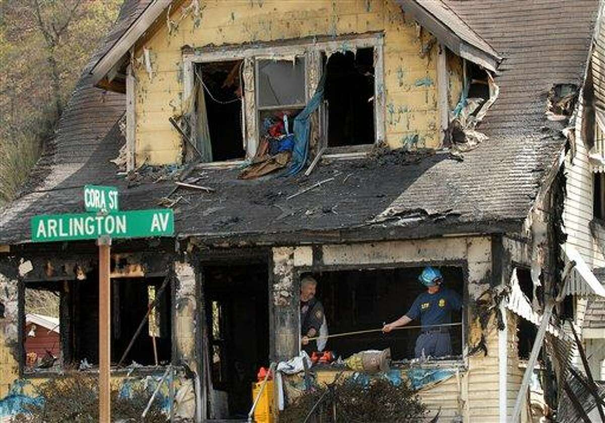 Investigators sift through debris in the aftermath of a house fire on Saturday in Charleston, W.Va. A fire tore through the two-story home that had no functioning smoke detectors, killing eight family members, including six children, Charleston Mayor Danny Jones said. Associated Press