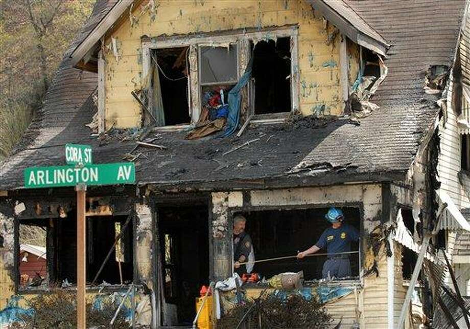 """Investigators sift through debris in the aftermath of a house fire on Saturday in Charleston, <a href=""""http://W.Va"""">W.Va</a>.  A fire tore through the two-story home that had no functioning smoke detectors, killing eight family members, including six children, Charleston Mayor Danny Jones said.  Associated Press Photo: AP / AP"""