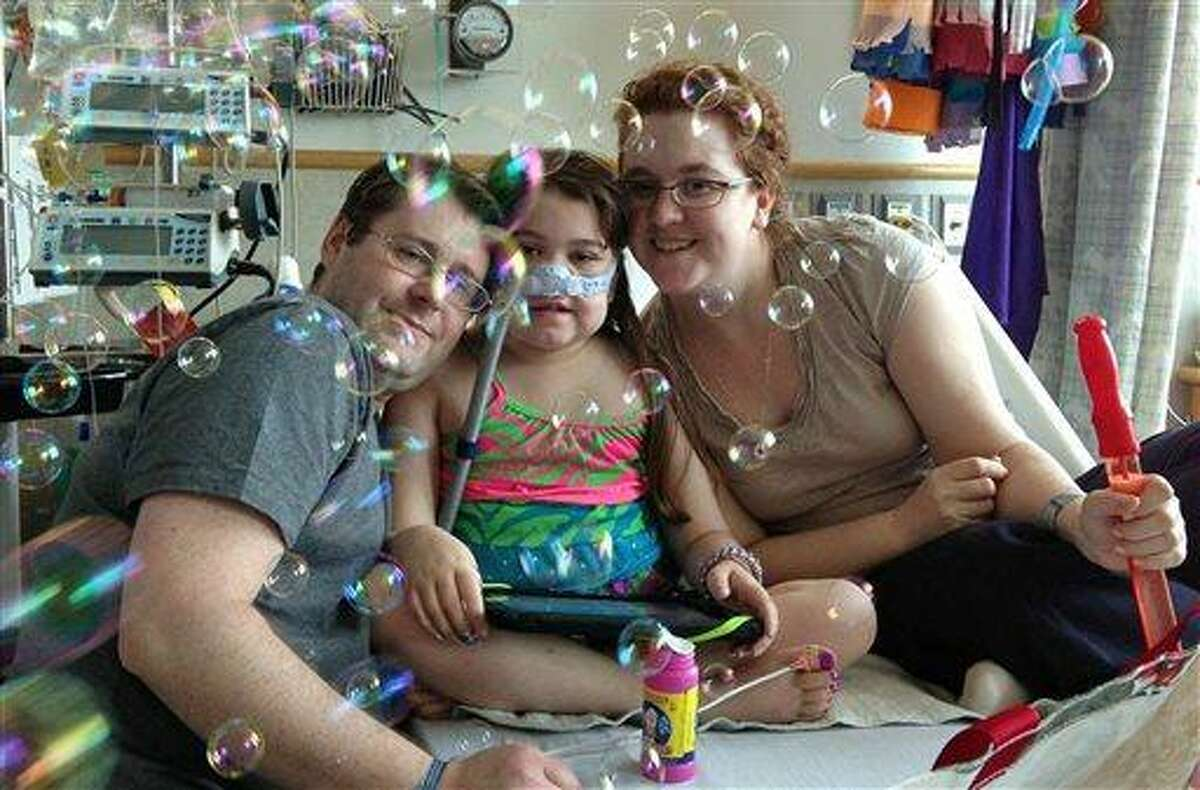 In this May 30, 2013 file photo provided by the Murnaghan family, Sarah Murnaghan, center, celebrates the 100th day of her stay in Children's Hospital of Philadelphia with her father, Fran, left, and mother, Janet. The 10-year-old suburban Philadelphia girl received a lung transplant there Wednesday, June 12, 2013, her family said. (AP Photo/Murnaghan Family, File)