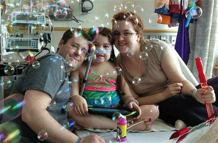 In this May 30, 2013 file photo provided by the Murnaghan family, Sarah Murnaghan, center, celebrates the 100th day of her stay in Children's Hospital of Philadelphia with her father, Fran, left, and mother, Janet. The 10-year-old suburban Philadelphia girl received a lung transplant there Wednesday, June 12, 2013, her family said. (AP Photo/Murnaghan Family, File) Photo: AP / Murnaghan Family