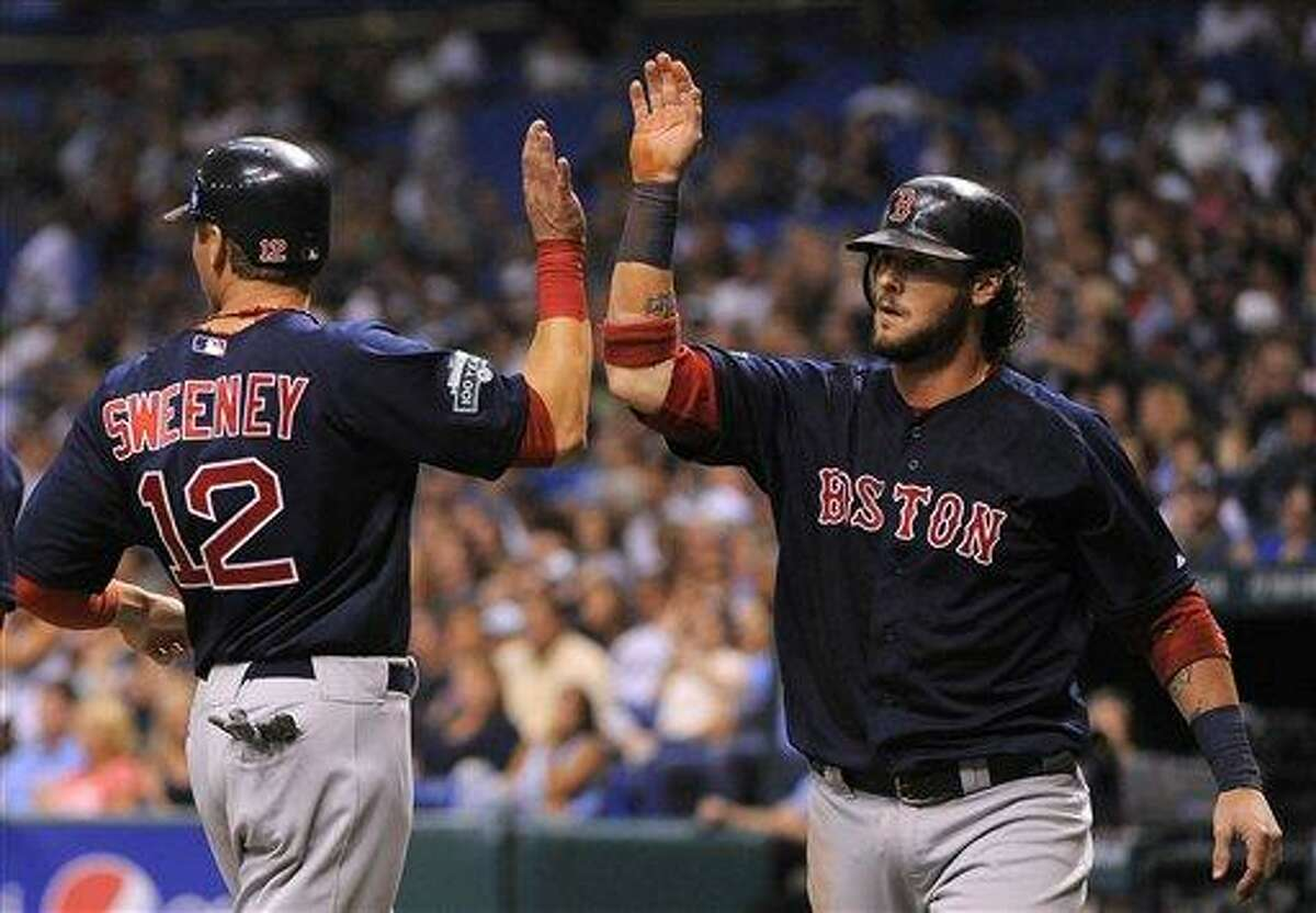 Boston Red Sox base runners Jarrod Saltalamacchia, right, and Ryan Sweeney celebrate at the plate after both scoring off of teammate Pedro Ciriaco's single off of Tampa Bay Rays starting pitcher Jeremy Hellickson during the second inning of a baseball game, Friday, July 13, 2012, in St. Petersburg, Fla. (AP Photo/Brian Blanco)
