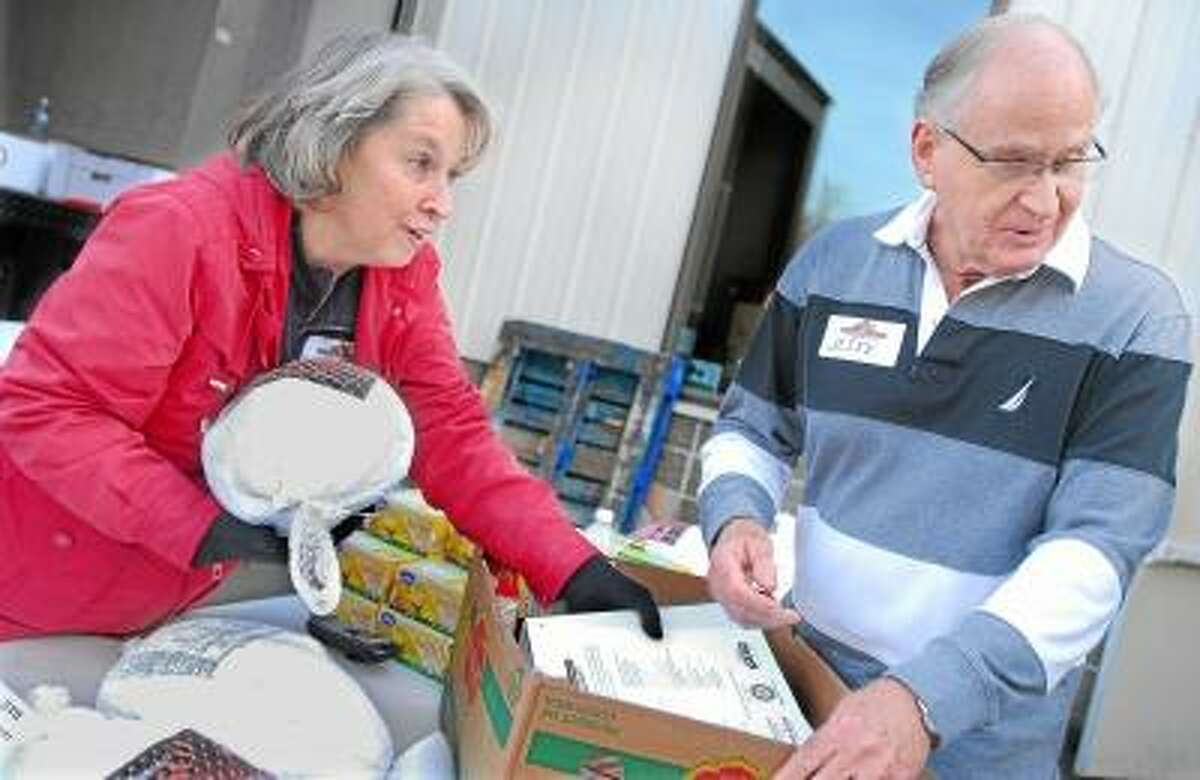 Catherine Avalone/The Middletown Press Volunteers Gerri Howard, a member of Fellowship Church and Jesse Glick, a member of the Middletown Interfaith Community distribute one of the 606 Thanksgiving baskets prepared by the members of the Middletown Community Thanksgiving Project Tuesday afternoon at Fellowship Church at 1002 Saybrook Road in Middletown. Each basket included a turkey, stuffing, potatoes, onions, can of cranberry sauce, yams, green beans and corn.