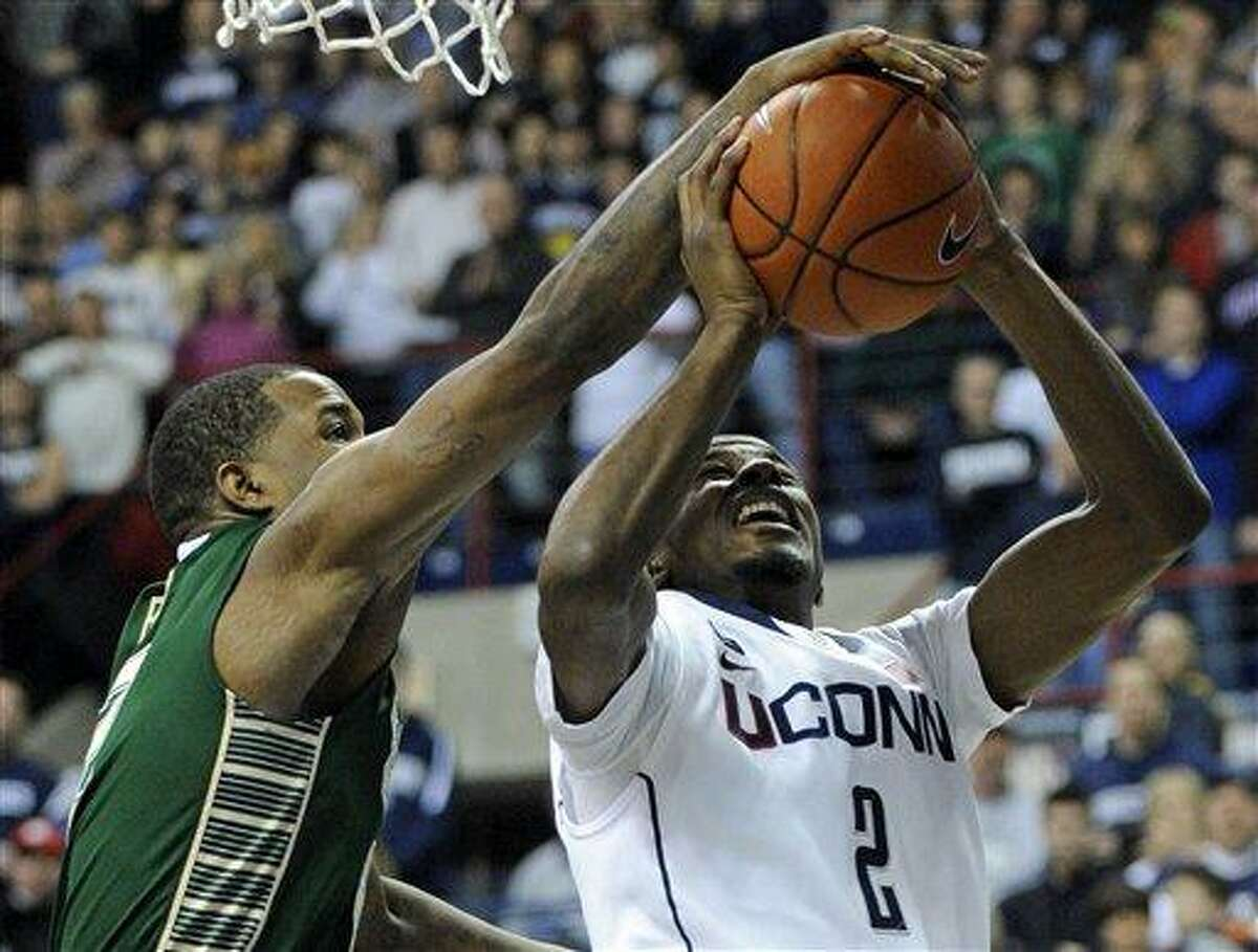 South Florida's Victor Rudd, left, blocks the shot of Connecticut's DeAndre Daniels during the first half of an NCAA college basketball game in Storrs, Conn., Sunday, Feb. 3, 2013. (AP Photo/Fred Beckham)