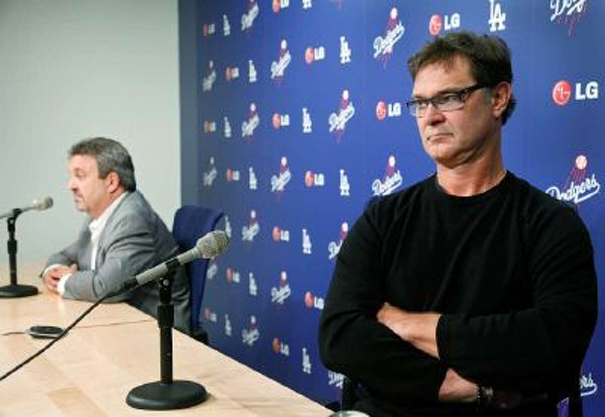 Los Angeles Dodgers General Manager Ned Colletti, left, and Dodgers Manager Don Mattingly speak to the media at Dodger Stadium in Los Angeles.