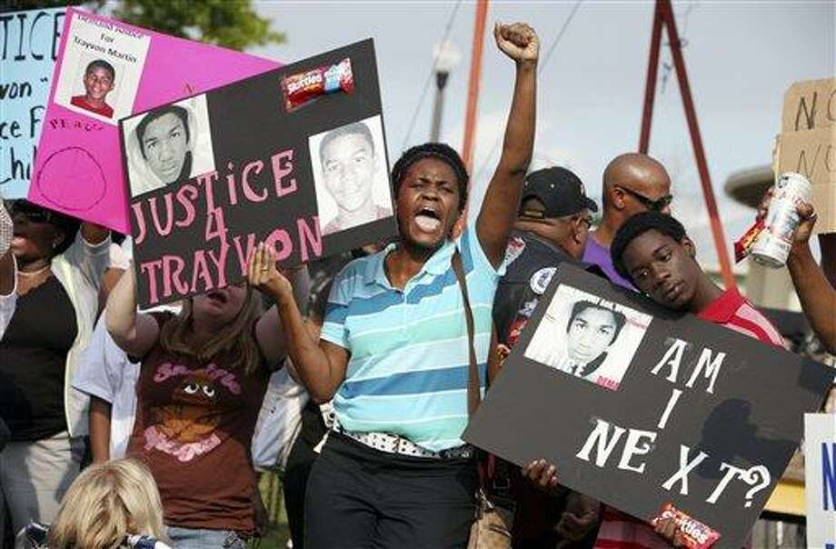 Protestors, Lakesha Hall, 32, of Sanford, center, and her son, Calvin Simms, 12, right, gather early for a rally for Trayvon Martin, the black teenager who was fatally shot by a neighborhood watch captain last month, at Fort Mellon Park in Sanford, Fla., Thursday. Associated Press Photo: AP / FR 170193AP