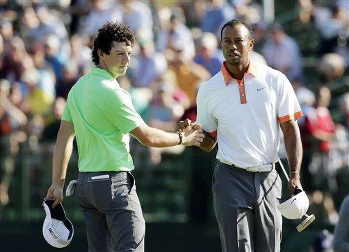 Rory McIlroy, left, of Northern Ireland, and Tiger Woods shake hands on the 18th green during practice for the U.S. Open golf tournament at Merion Golf Club, Wednesday, June 12, 2013, in Ardmore, Pa. (AP Photo/Charlie Riedel)