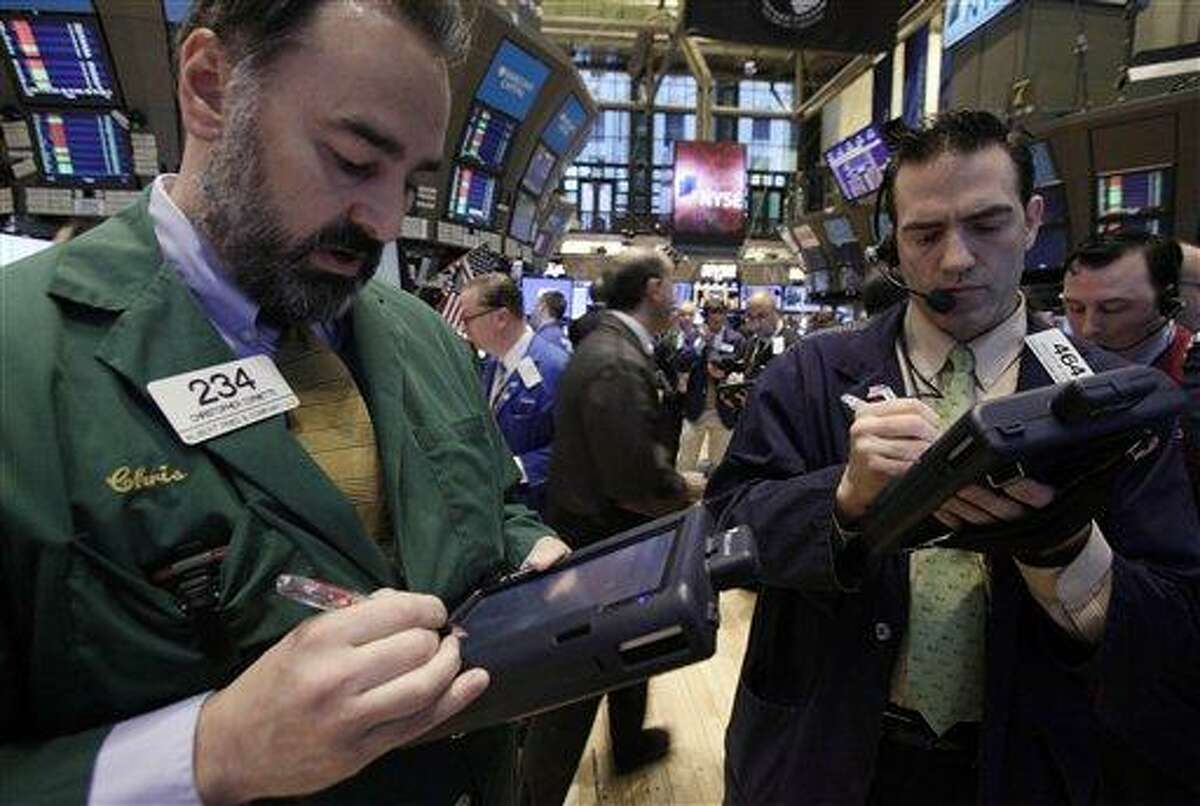 In a file photo, traders Christopher Cornette, left, and Gregory Rowe work on the floor of the New York Stock Exchange. Wall Street futures rose early Friday as traders awaited the release of U.S. housing data. Associated Press