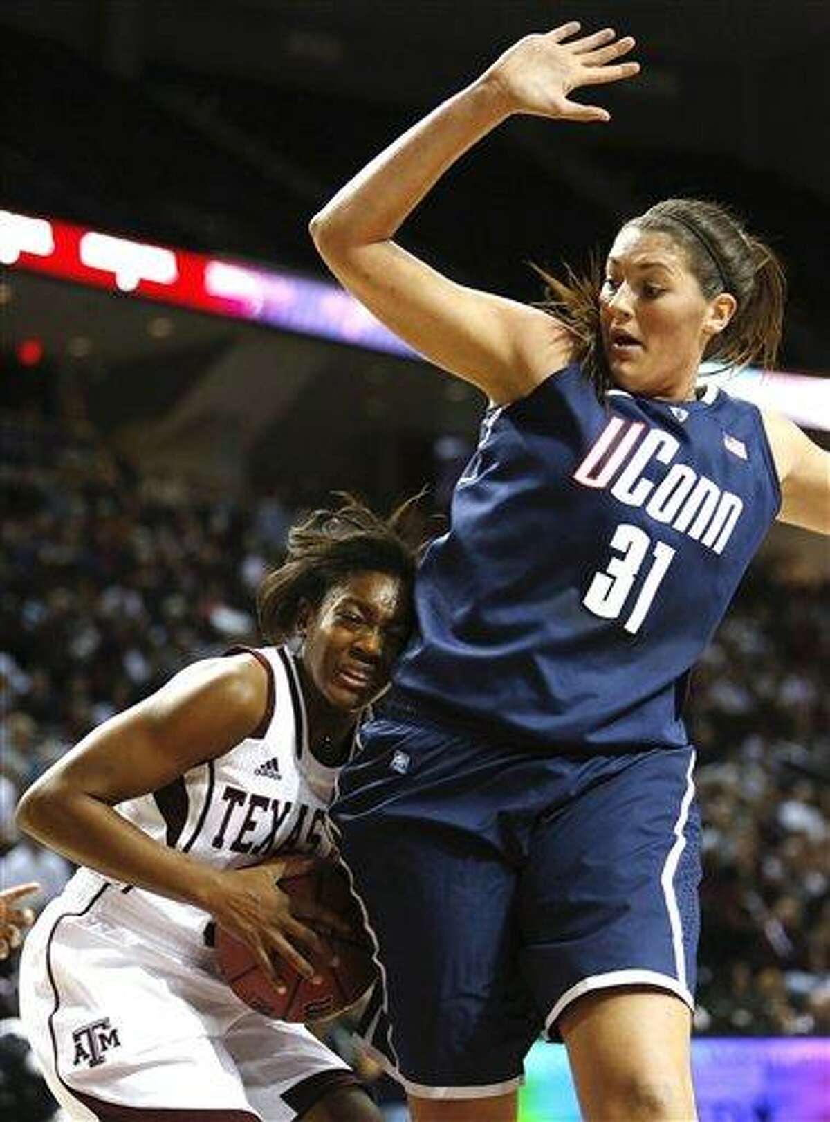Texas A&M's Courtney Walker, left, attempts to drive the ball against Connecticut defender Stefanie Dolson (31) during the first half of a NCAA college basketball game Sunday, Nov. 18, 2012, in College Station, Texas. (AP Photo/Jon Eilts)