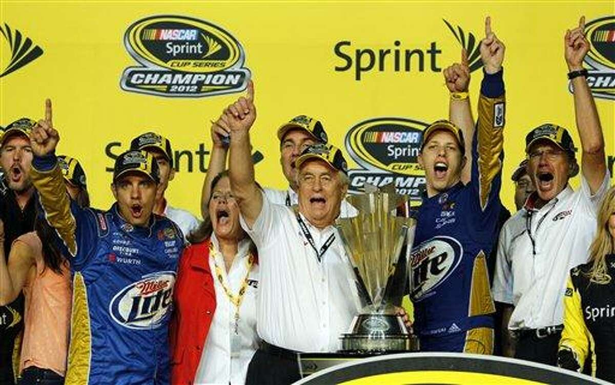 Driver Brad Keselowski, second from right, joins team owner Roger Penske, second from left and crew chief Paul Wolf and others celebrating the NASCAR championship tittle trophy at Homestead-Miami Speedway Sunday, Nov. 18, 2012 in Homestead, Fla. (AP Photo/Terry Renna)