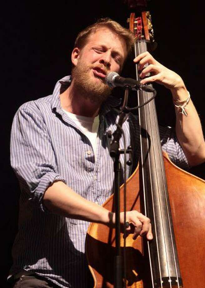 FILE - This Feb. 16, 2013 file photo shows Ted Dwane, of the English folk rock band Mumford & Sons, performing at the Susquehanna Bank Center in Camden, N.J. Dwane has a blood clot on his brain that will require surgery. The Grammy Award-winning folk-rock group has postponed concerts Tuesday, June 11, in Dallas, Wednesday June 12 in The Woodlands and Thursday, June 13 in New Orleans. A statement on its website said there are no plans to postpone or cancel any other appearances on the current tour. Mumford & Sons has a headlining gig Saturday at the Bonnaroo Music & Arts Festival in Manchester, Tenn. (Photo by Owen Sweeney/Invision/AP, file) Photo: AP / Invision