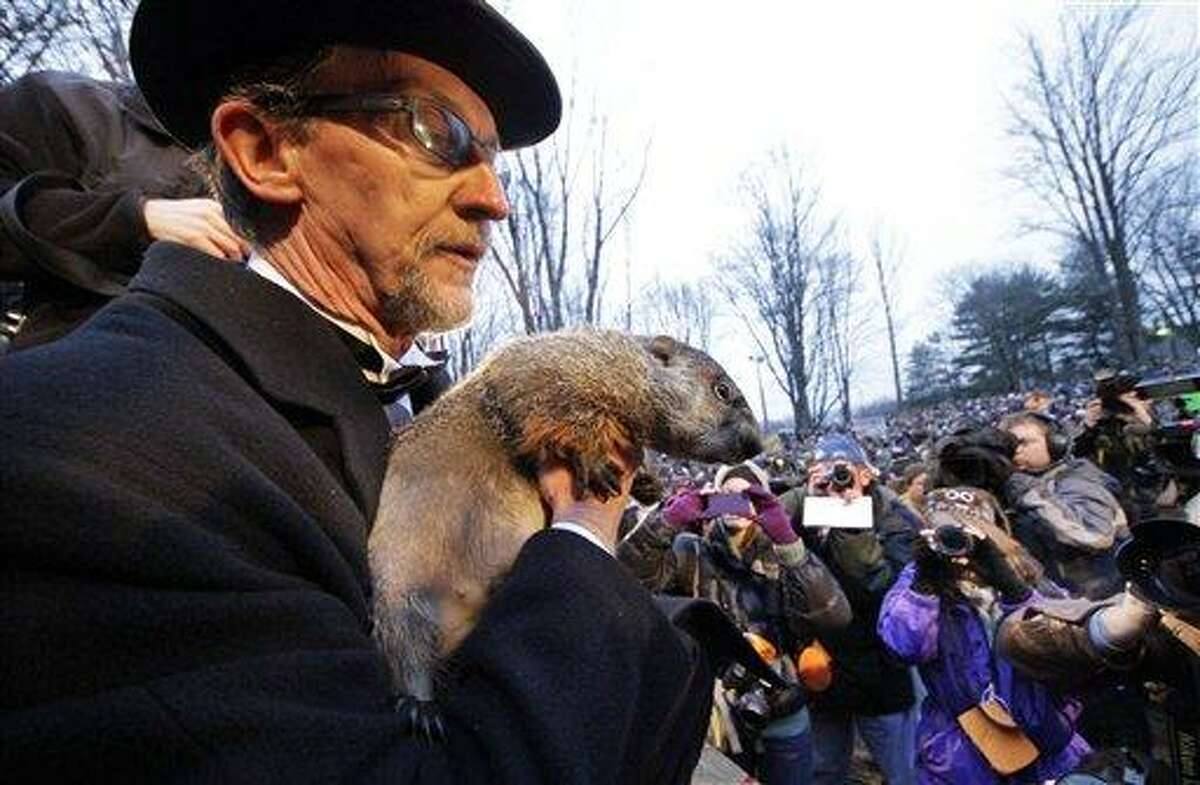 FILE - In this Feb. 2, 2012 file photo, Groundhog Club handler Ron Ploucha holds Punxsutawney Phil, the weather prognosticating groundhog, during the 126th celebration of Groundhog Day on Gobbler's Knob in Punxsutawney, Pa. Groundhog Day is Saturday, and the community is holding its welcome-back bash for the famous winter-weather prognosticator _ the so-called seer of seers and sage of sages. Legend has it that if the groundhog sees his shadow on Feb. 2, winter will last six more weeks. No shadow means an early spring. (AP Photo/Gene J. Puskar, File)