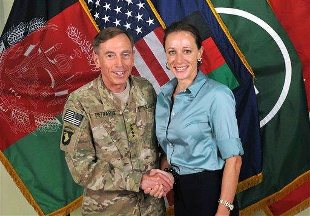 Davis Petraeus, left, shaking hands with Paula Broadwell, co-author of his biography