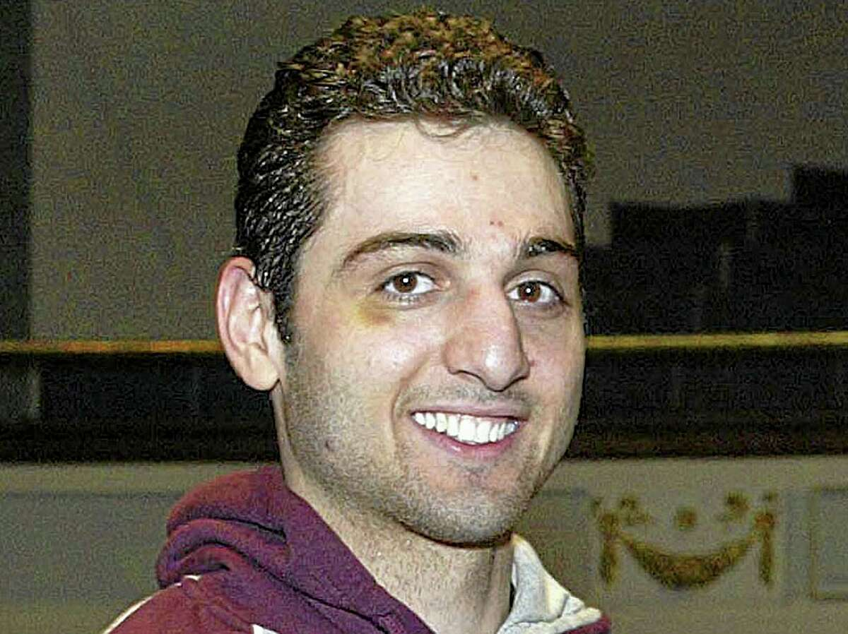 FILE - In this Feb. 17, 2010, file photo, Tamerlan Tsarnaev smiles after accepting the trophy for winning the 2010 New England Golden Gloves Championship in Lowell, Mass. Tamerlan and Dzhokhar Tsarnaev befriended Donald Larking, a brain-damaged anti-U.S. government conspiracy theorist, through their mother's health care aide job years before the deadly attack, a lawyer for Larking's family said Tuesday, Aug. 6, 2013. (AP Photo/The Lowell Sun, Julia Malakie File) MANDATORY CREDIT