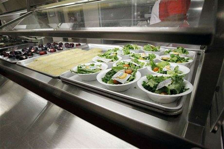 FILE - In this Sept. 12, 2012 file photo, side salads, apple sauce and plums  await the students of Eastside Elementary School in Clinton, Miss. The government for the first time is proposing broad new standards to make school snacks healthier, a move that would ban the sale of almost all candy, high-calorie sports drinks and greasy foods on campus.  (AP Photo/Rogelio V. Solis, File) Photo: AP / AP