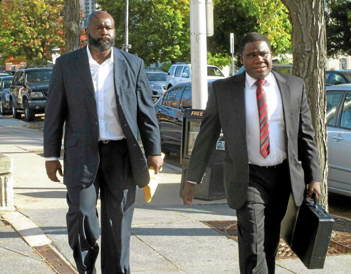 Former NFL defense end Hugh Douglas, left, walks with his lawyer, Corey Brinson, to Hartford Superior Court, Monday, Oct. 21, 2013, in Hartford, Conn. Douglas, who played for the New York Jets, Philadelphia Eagles and Jacksonville Jaguars from 1995 to 2004, pleaded not guilty to allegations he assaulted his girlfriend at a Hartford hotel in September. (AP Photo/Dave Collins)