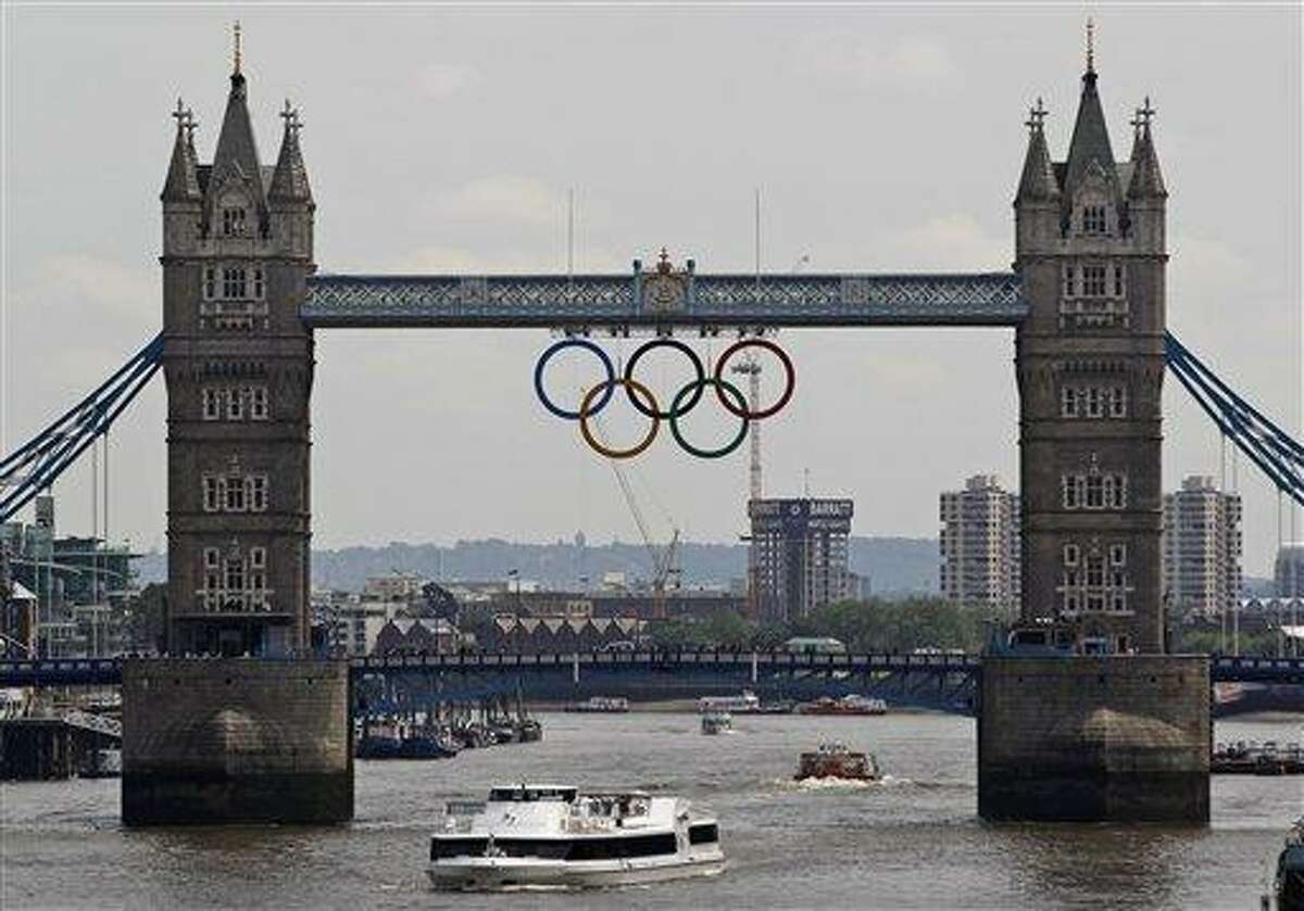 FILE This Wednesday, June 27, 2012 file photo shows the Olympic rings atop the iconic Tower Bridge over the river Thames in London, with one month to go until the start of London 2012 Games. The 2012 Olympics will showcase a much different London and a much different event from the 1948 London Olympics which was hosted amid severe austerity in the aftermath of World War II. This will be a $14.5 billion extravaganza featuring multimillionaire professionals and global stars like Usain Bolt and Michael Phelps, shiny new purpose-built venues and a revitalized east London. Britain's biggest peacetime project also comes with a massive security operation. (AP Photo/Lefteris Pitarakis, file)