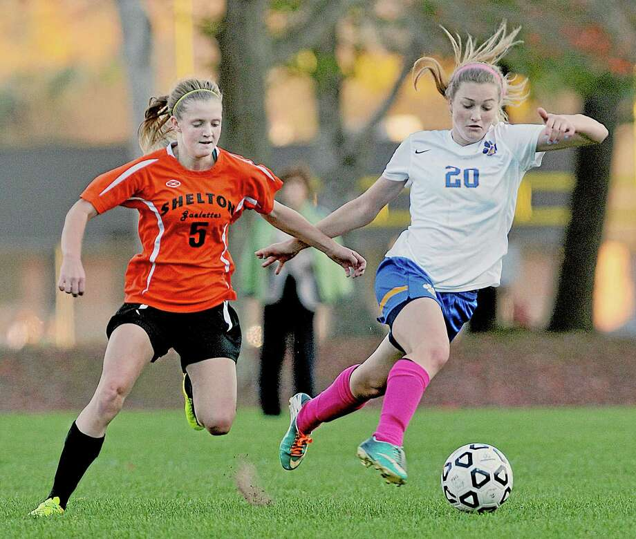 Mercy junior midfielder Kendra Landy moves the ball past Shelton's Laurel Bailey Monday afternoon at the home field of the Tigers. Landy assisted Olivia Ozcyz in her first of four goals. Bailey scored in the first half for the Gaels. Mercy won, 6-1. Photo: Catherine Avalone — The Middletown Press  / TheMiddletownPress